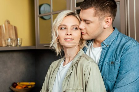 smiling young loving couple hugging in kitchen at home
