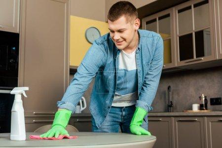 Photo pour Homme souriant dans des gants de caoutchouc table de nettoyage avec chiffon et détergent dans la cuisine à la maison - image libre de droit