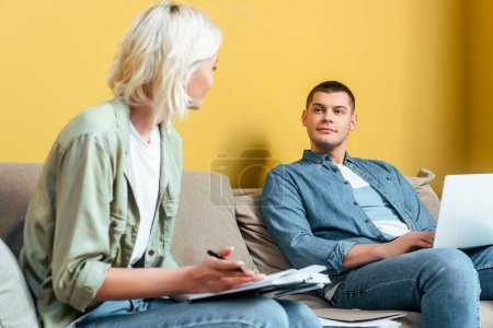 Photo for Selective focus of young freelance couple on sofa using laptop and writing in notebook near yellow wall - Royalty Free Image