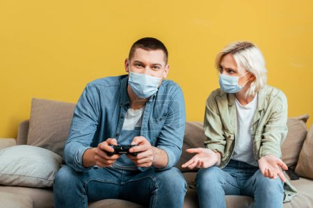 Photo for KYIV, UKRAINE - APRIL 22, 2020: young man in medical mask playing video games with displeased girlfriend on sofa near yellow wall - Royalty Free Image