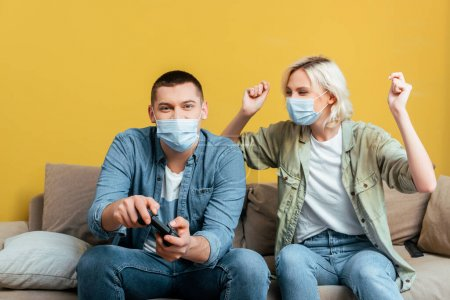 Photo for KYIV, UKRAINE - APRIL 22, 2020: young man in medical mask playing video games with cheerful girlfriend on sofa near yellow wall - Royalty Free Image