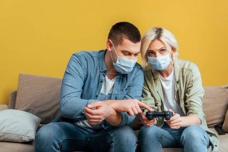 Photo for KYIV, UKRAINE - APRIL 22, 2020: young man in medical mask teaching girlfriend playing video games on sofa near yellow wall - Royalty Free Image
