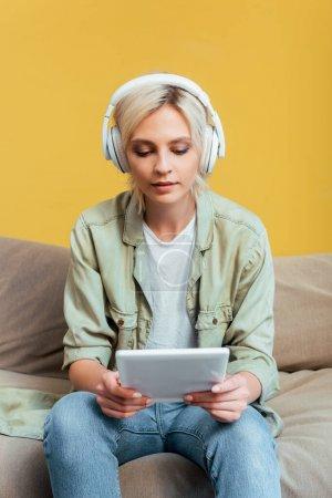 jeune femme blonde en casque avec tablette numérique sur canapé près du mur jaune
