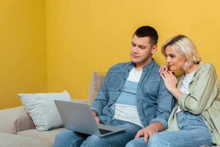 Photo for Young couple on sofa sitting with laptop near yellow wall - Royalty Free Image