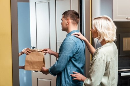 Photo for Delivery man giving package to young couple near open door at home - Royalty Free Image
