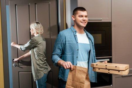Photo pour Homme souriant avec boîtes à pizza et paquet près de la porte de fermeture petite amie à la maison - image libre de droit