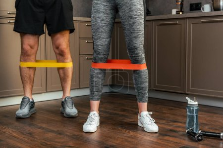 Photo for Cropped view of couple exercising together with resistance bands on legs at home during quarantine - Royalty Free Image
