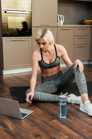 Photo for Young sportswoman having online training on laptop at home during quarantine - Royalty Free Image