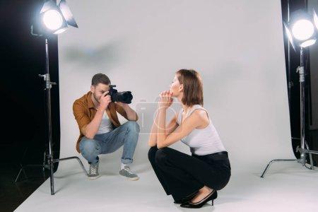 Photo pour Photographe prenant une photo de modèle attrayant dans le studio de photo - image libre de droit