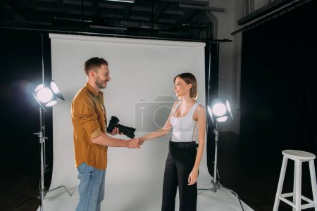Photo for Side view of photographer holding digital camera while shaking hands with smiling model in photo studio - Royalty Free Image