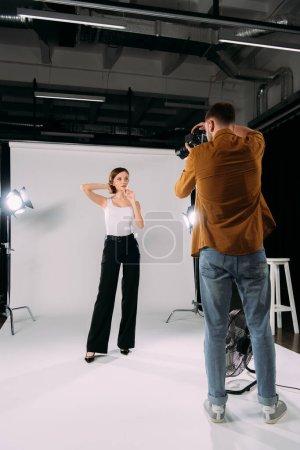 Photo pour Photographe travaillant avec un jeune modèle attrayant en studio photo - image libre de droit