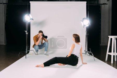 Photo pour Photographe tenant un appareil photo numérique tout en prenant une photo de jeune modèle sur le sol dans un studio photo - image libre de droit