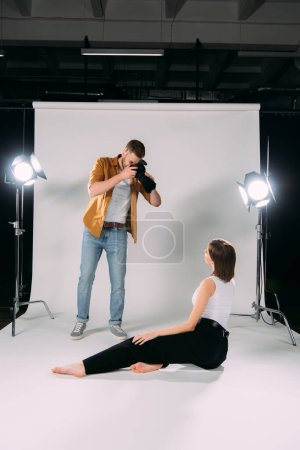 Photo for Photographer using digital camera while working with model in photo studio - Royalty Free Image