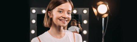 Photo pour Belle jeune femme souriante à la caméra en studio photo, culture panoramique - image libre de droit