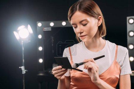 Photo pour Belle femme tenant visage poudre et pinceau cosmétique en studio photo - image libre de droit