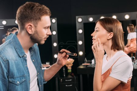 Photo for Side view of model pointing on cheek near makeup artist holding cosmetic brush in photo studio - Royalty Free Image