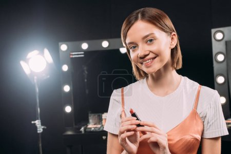 Beautiful smiling woman holding red lipstick in photo studio