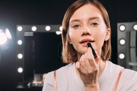 Photo pour Femme attrayante regardant un appareil photo en appliquant un rouge à lèvres dans un studio de photographie - image libre de droit