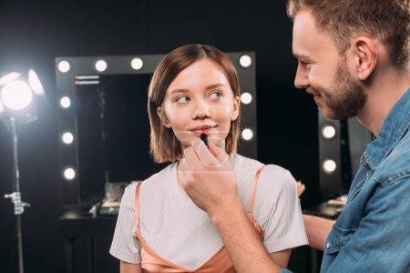 Foto de Sonriente artista de maquillaje aplicando lápiz labial rojo en atractiva modelo joven en el estudio de fotos - Imagen libre de derechos