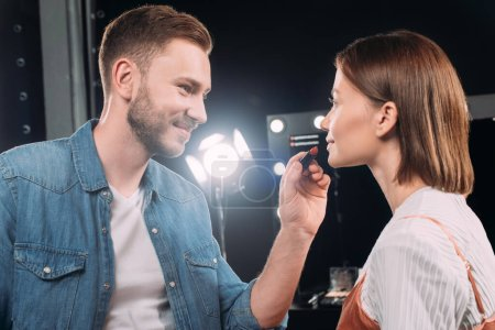 Handsome makeup artist smiling while applying lipstick on attractive model