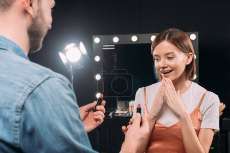 Photo for Selective focus of makeup artist holding lipsticks near surprised model in photo studio - Royalty Free Image