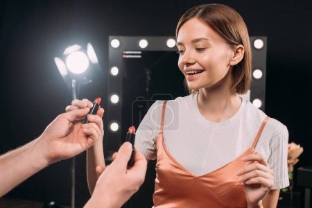 Photo for Smiling model taking lipstick from makeup artist in photo studio - Royalty Free Image