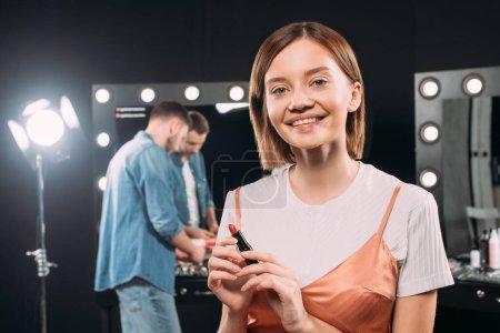 Photo pour Belle maquette souriante regardant l'appareil photo tout en tenant le rouge à lèvres dans le studio de photographie - image libre de droit