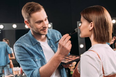 Photo for Smiling makeup artist applying blush on young model in photo studio - Royalty Free Image