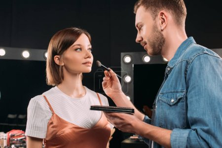 Photo pour Beau maquilleur tenant ensemble de maquillage et pinceau cosmétique près de belle jeune femme en studio photo - image libre de droit