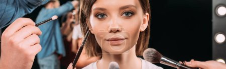 Photo for Panoramic orientation of makeup artists holding cosmetic brushes near beautiful model in photo studio - Royalty Free Image