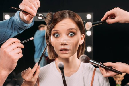 Photo for Makeup artist holding cosmetic brushes near shocked model looking at camera in photo studio - Royalty Free Image