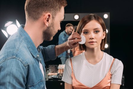 Foto de Maquillaje artista sosteniendo almohadilla de algodón cerca de la cara de la hermosa mujer en estudio de fotos - Imagen libre de derechos
