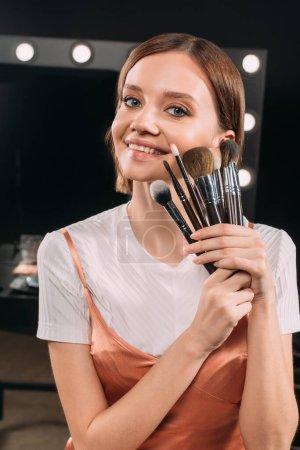Photo pour Belle femme tenant des pinceaux cosmétiques et souriant à la caméra dans le studio photo - image libre de droit