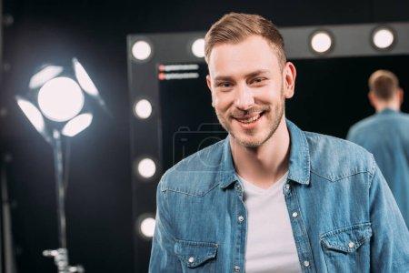 Photo pour Maquilleur beau sourire à la caméra dans le studio photo - image libre de droit