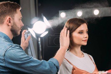 Photo pour Beau maquilleur utilisant la laque à cheveux tout en faisant coiffure à beau modèle en studio photo - image libre de droit