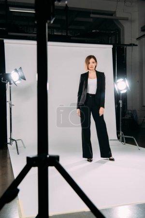 Photo pour Mise au point sélective d'un beau modèle élégant regardant la caméra près des projecteurs dans le studio photo - image libre de droit