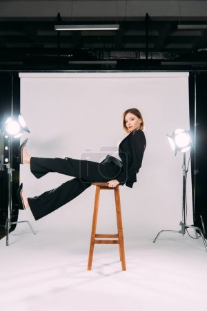 Photo for Side view of stylish model looking at camera while sitting on chair in photo studio - Royalty Free Image