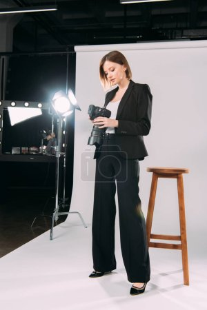 Photo pour Beau modèle regardant l'affichage de l'appareil photo numérique dans le studio photo - image libre de droit