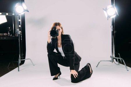 Photo pour Modèle élégant prenant des photos avec appareil photo numérique en studio photo - image libre de droit