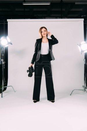 Photo pour Beau modèle en tenue formelle appareil photo numérique près des projecteurs dans le studio photo - image libre de droit