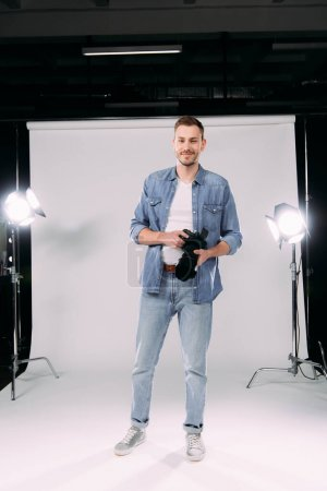 Handsome photographer holding digital camera and smiling at camera in photo studio