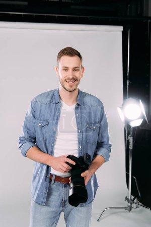 Photo pour Photographe tenant un appareil photo numérique et souriant en studio photo - image libre de droit