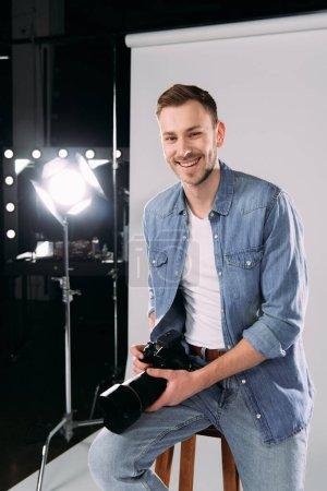 Photo pour Photographe souriant tenant un appareil photo numérique près d'un projecteur dans un studio photo - image libre de droit
