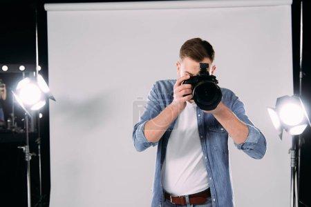 Photo pour Photographe photographiant avec un appareil photo numérique en studio - image libre de droit