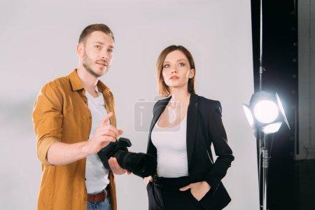 Photo pour Beau photographe pointant du doigt près du beau modèle en studio photo - image libre de droit