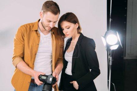 Photo pour Beau photographe et modèle élégant regardant l'affichage de l'appareil photo numérique dans le studio photo - image libre de droit