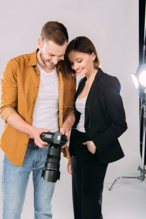 Photo for Handsome photographer and beautiful smiling woman looking at display of digital camera in photo studio - Royalty Free Image