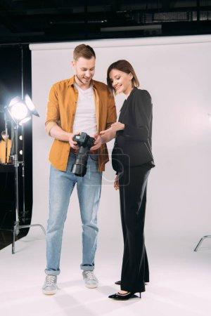 Photo pour Beau modèle souriant pointant avec la main à l'affichage de l'appareil photo numérique près beau photographe en studio photo - image libre de droit