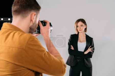 Photo pour Selective focus of elegant model posing at photographer with digital camera in photo studio - image libre de droit