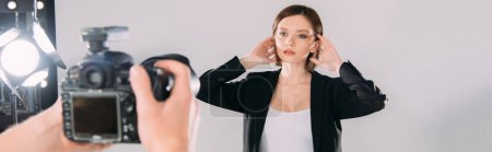Photo for Selective focus of beautiful stylish model posing at photographer with digital camera in photo studio - Royalty Free Image